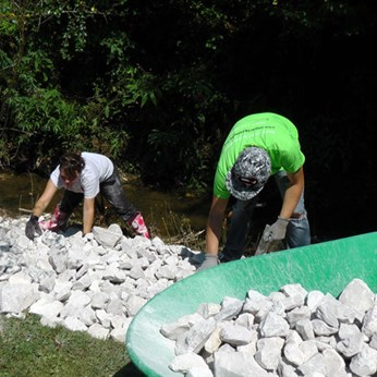 Moving rock to stabilize a creek bank in Johnson County